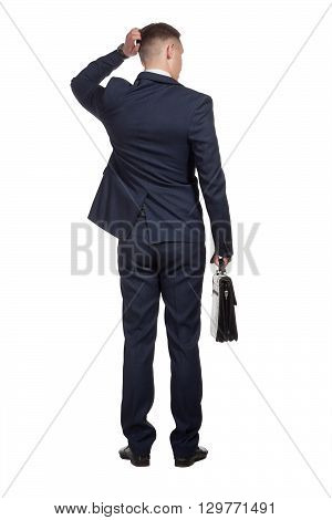 Young businessman standing, holding briefcase in his hand and making a difficult decision, isolated on white background.