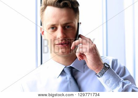 business people and office concept - young businessman calling on smartphone over office near with window