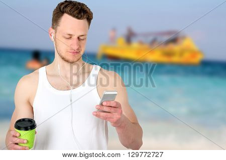 Portrait of a happy sports man standing near sport field with a mobile phone outdoors
