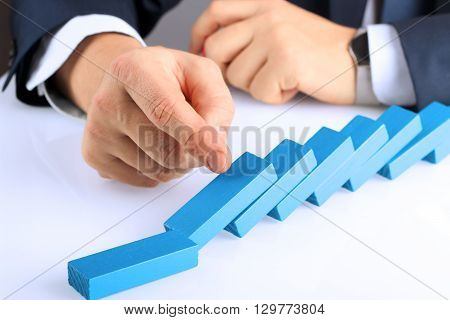 Planning risk and strategy in business businessman pushing wooden block