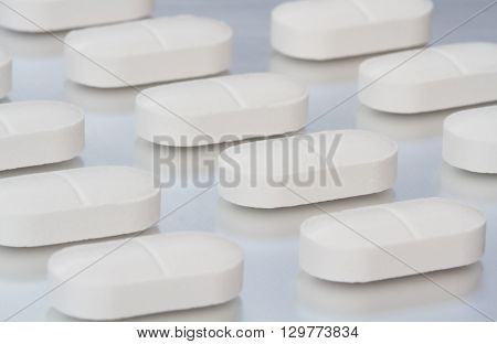 Lines of white painkilling pills, tablets and drugs on a shiny, silver background.