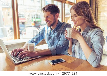 Beautiful young couple is using a laptop talking and smiling while sitting in the cafe. Girl is holding a cup of hot drink