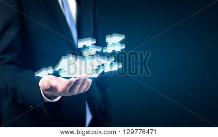 Businessperson holding abstract puzzle pieces on dark background