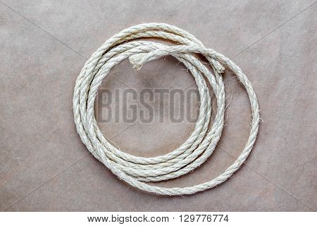 rope coiled at kraft paper on the background close up