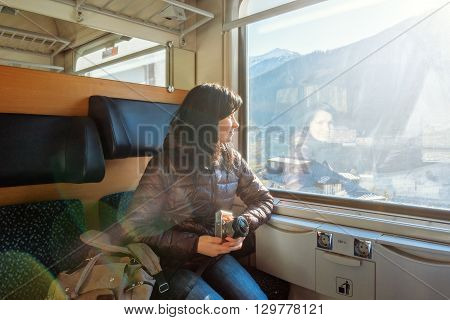 Young woman traveling by train sitting at the window with a camera in his hands. Traveling by train at the Alpine Railroad