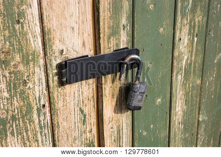 Wooden gates with a fitted padlock which is open.