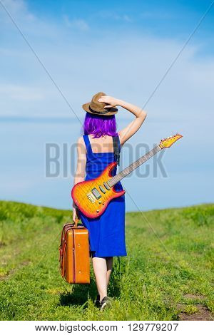Young Woman With Suitcase And Guitar