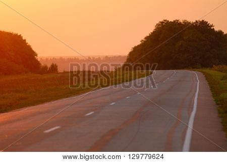 Old asphalt road at sunset autumn season