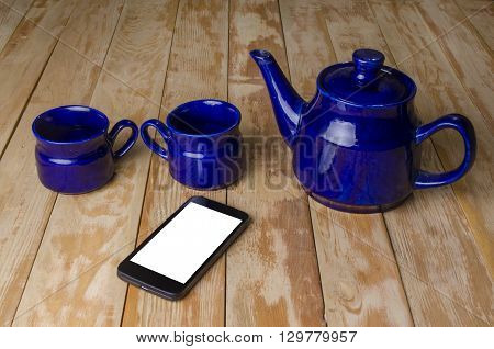 blue ware for tea and phone on a wooden board