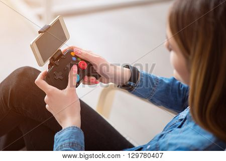 Professional player   Close up of game console in hands of pleasant woman holding it and using while resting