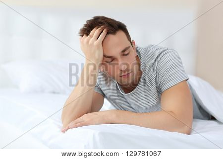 Sleepy young man in bed at home