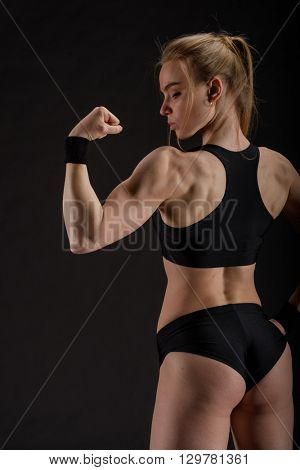 Young muscular woman posing on black background