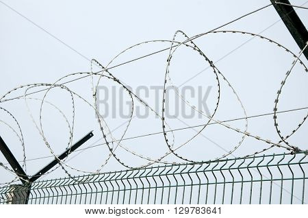 Barbed wire on the fence of the construction of the Kerch bridge closeup
