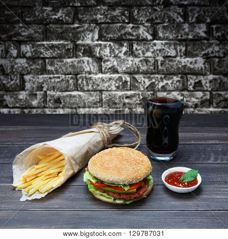Fast food. Hamburger, potato fries, cola drink. Takeaway food. Wrapped French fries, packaging, Cola glass, tomato sauce, double cheese hamburger at rustic wood and grey brickwall background.