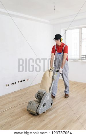 Worker polishing hardwood parquet floor with grinding machine.