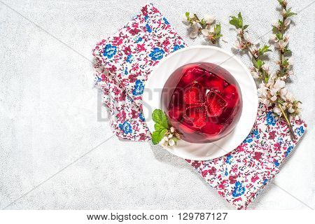 Delicious cherry jelly with whole berries on the plate and flowering branches of cherry on colored napkin and white background with space for text