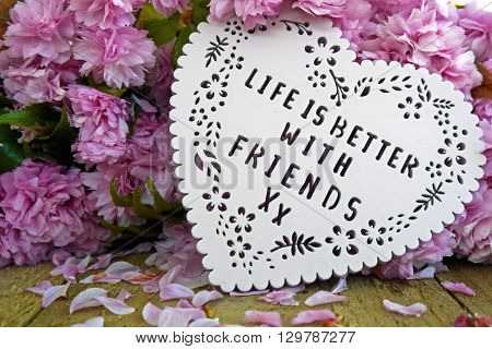 Life is better with friends heart shaped plaque with a blossom background