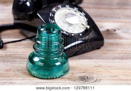 Close up of an antique electric glass insulator with vintage manual dial phone in background. Rustic wood underneath telecommunication objects.
