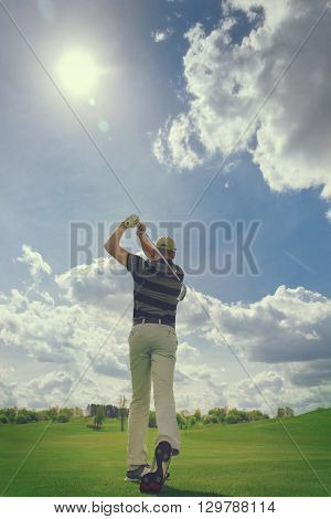 Male golf player hitting from fairway on golf course at sunny day
