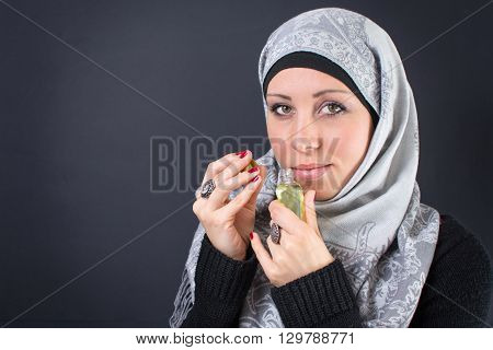 Muslim Woman In Hijab With A Perfume