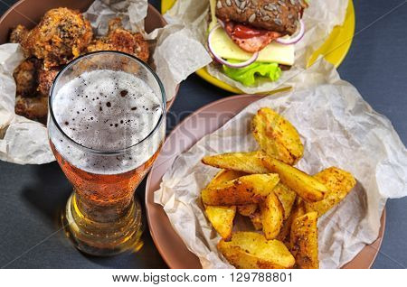 Top view of glass of beer, fries, sandwich and chicken legs on black slate stone