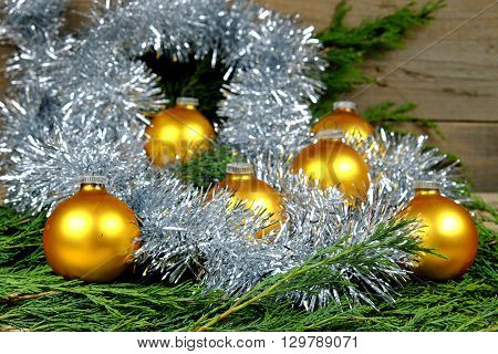 Christmas balls in a gold-colored chain around them in the color silver on an old wooden table with green needles