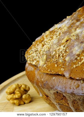Cake with cream and walnuts. Cake, walnuts, cream on wooden board, isolated, black background