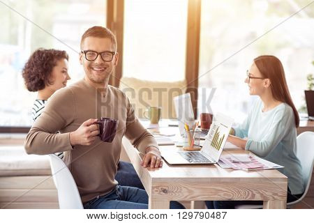Enjoyable time. Cheerful delighted smiling handsome man holding cup and drinking coffee while his colleagues talking in the background