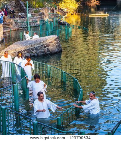 YARDENIT, ISRAEL - JANUARY 21, 2012: Christian pilgrims enter Jordan River waters. They make a baptism ceremony in honor of Jesus Christ's baptism here