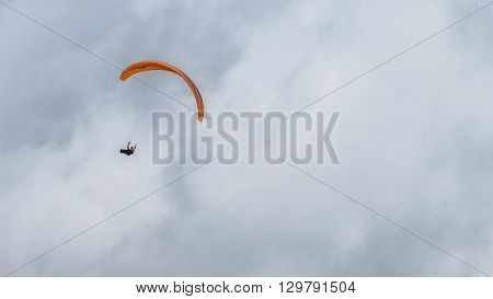 Single parachutist soar in tje cloudy sky