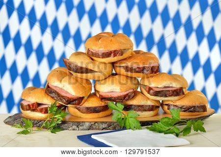 Traditional oven fresh Bavarian meat loaf on crisp rolls, the Bavarian flag in the background