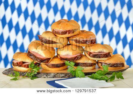 Traditional oven fresh Bavarian meat loaf on crisp rolls, the Bavarian flag in the background