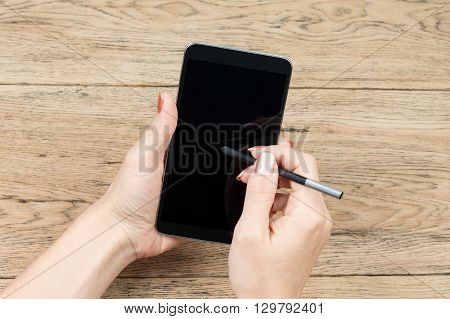 On old wooden table, one female hand holding a large smartphone, and the other writing on stylus it