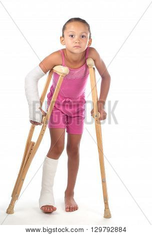 A young girl struggles to walk with crutches after injuries to her arm and leg.
