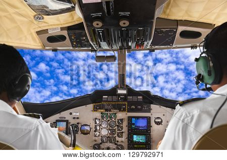 Pilots in the plane cockpit and cloudy sky - transportation background