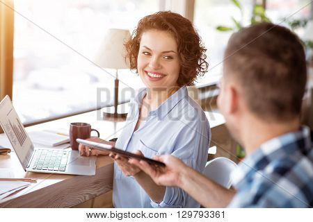 Here you are.  Overjoyed delighted smiling woman at the table and working on the laptop while getting tablet from her male colleague