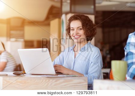 Ready to show the result. Pleasant delighted smiling woman sitting at the table and using laptop while working with her colleagues