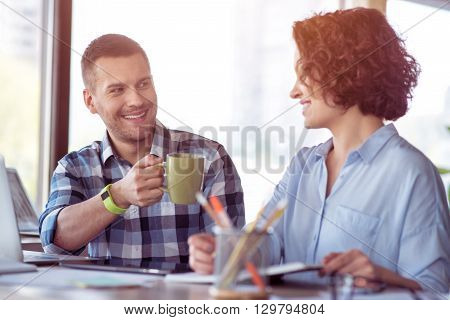 Lets rest. Pleasant handsome smiling man holding cup and drinking coffee while sitting at the table with her colleague