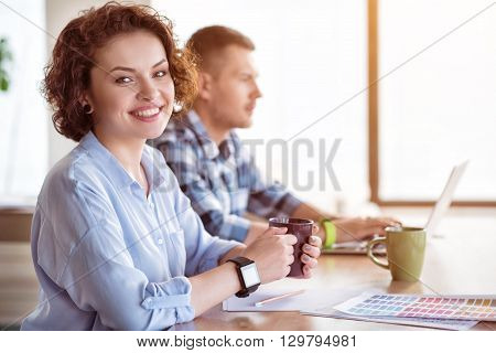Enjoy every day. Pleasant cheerful woman drinking coffee and sitting at the table while her colleague  working on the laptop in the background
