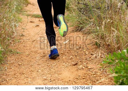 Close Up Of Woman's Feet Running On Footpath From Behind