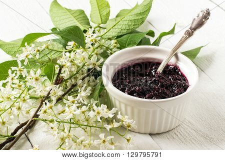Medicinal plant - bird cherry (Prunus padus). Flowering branches and jam on a white wooden background