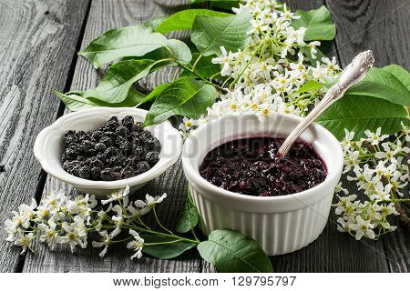 Medicinal plant - bird cherry (Prunus padus). Flowering branches dried berries and jam on a white wooden background. Selective focus