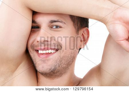 Handsome young man is satisfied with his skin. He is raising his arms under head and smiling. Man is standing with naked body