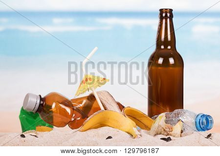 Beer bottle, food and household waste in the sand on the seashore.