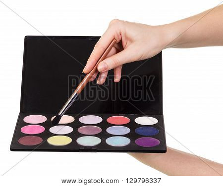 Female hand with a brush and colorful eyeshadows isolated on white background.