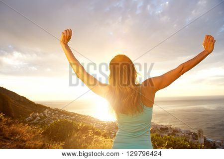 Back Of Woman With Arms Outstretched During Sunset