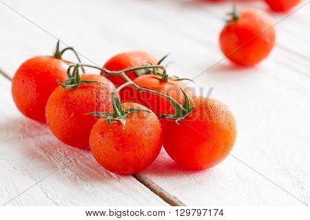 fresh ripe small tomatoes on wood background