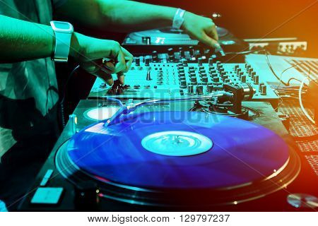 Dj mixes the track in the nightclub at party. Vinyl Player in foreground