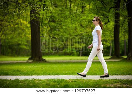 Middle-age woman walking in city park