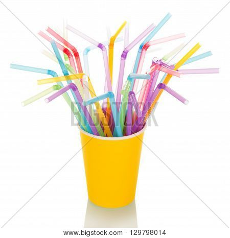 Multi-colored straws for a cocktail in a disposable cup isolated on a white background.